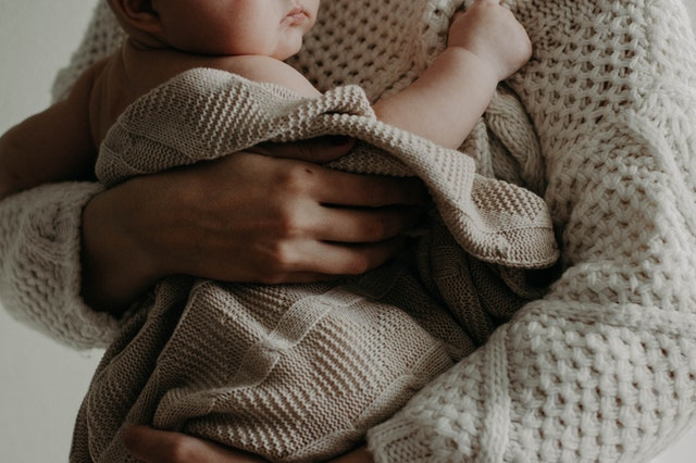Close up of a baby being held by someone in a beige knit sweater